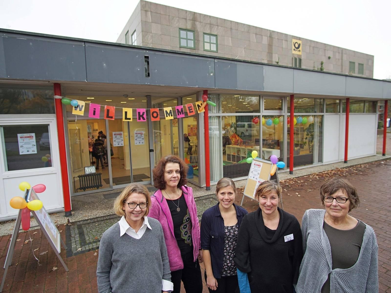 Fünf Frauen vor einem Gebäude.