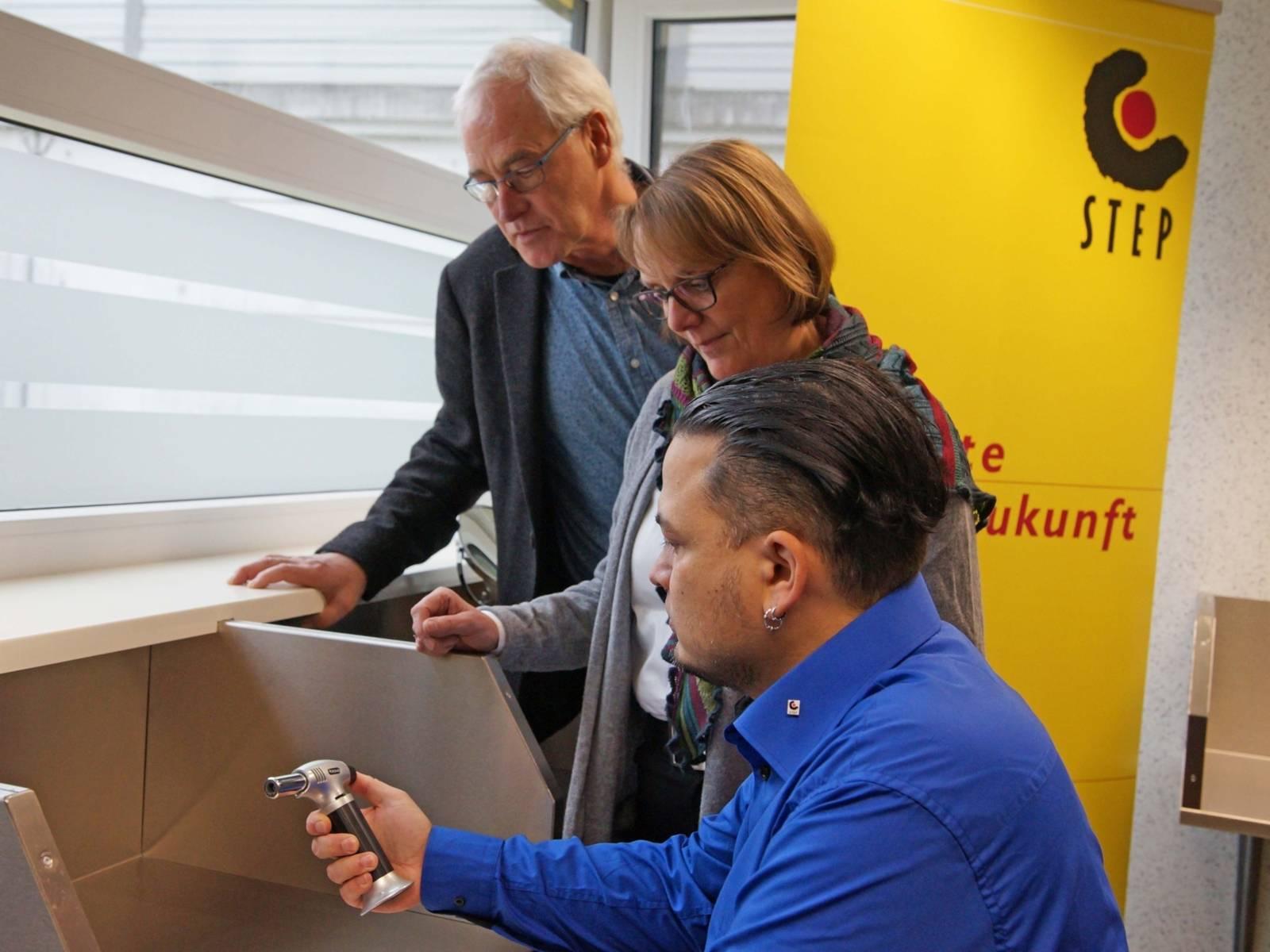 Ein Mann zeigt einer Frau und einem weiteren Mann ein technisches Gerät.