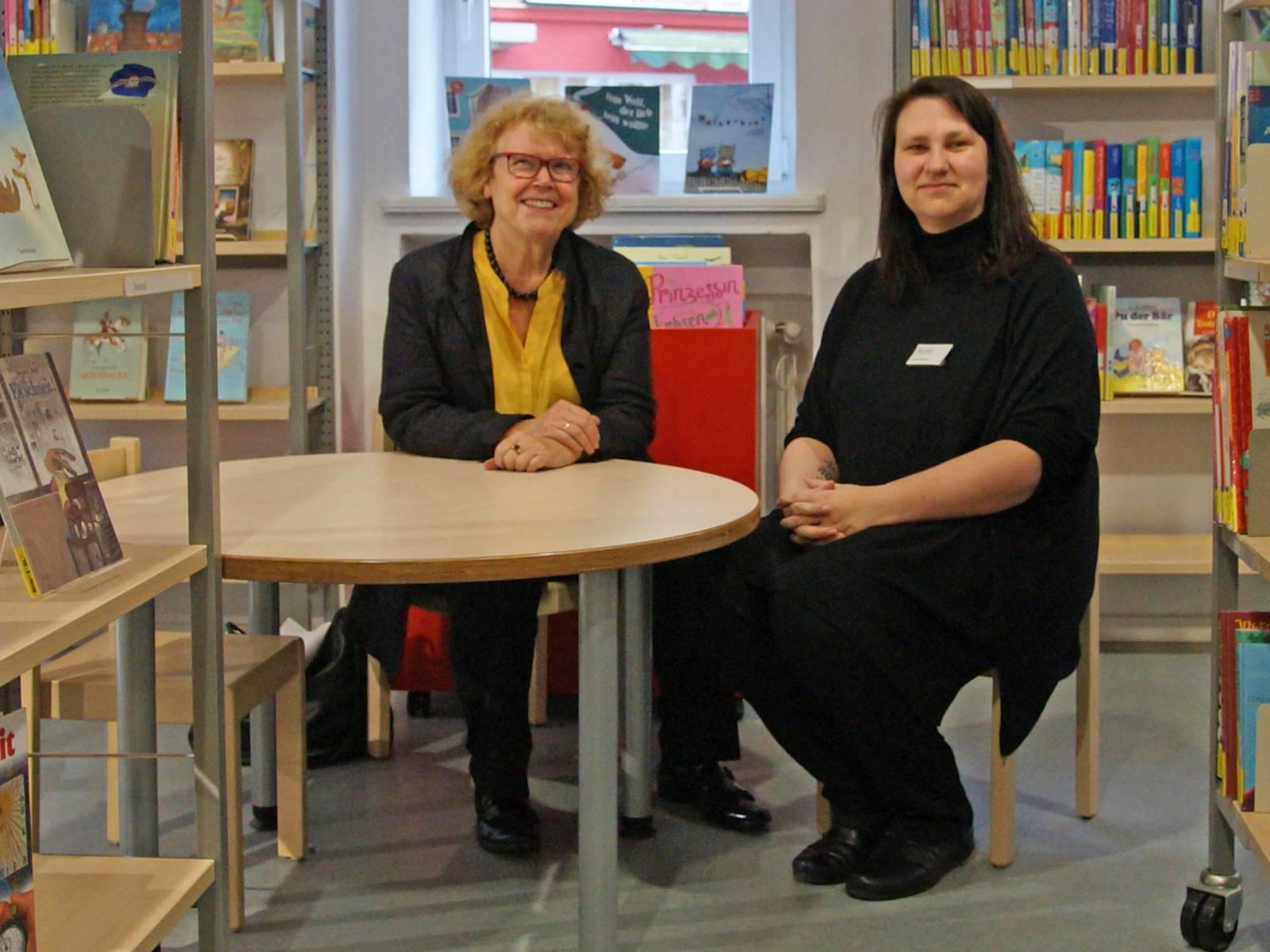 Zwei Frauen an einem Tisch inmitten von Büchern.