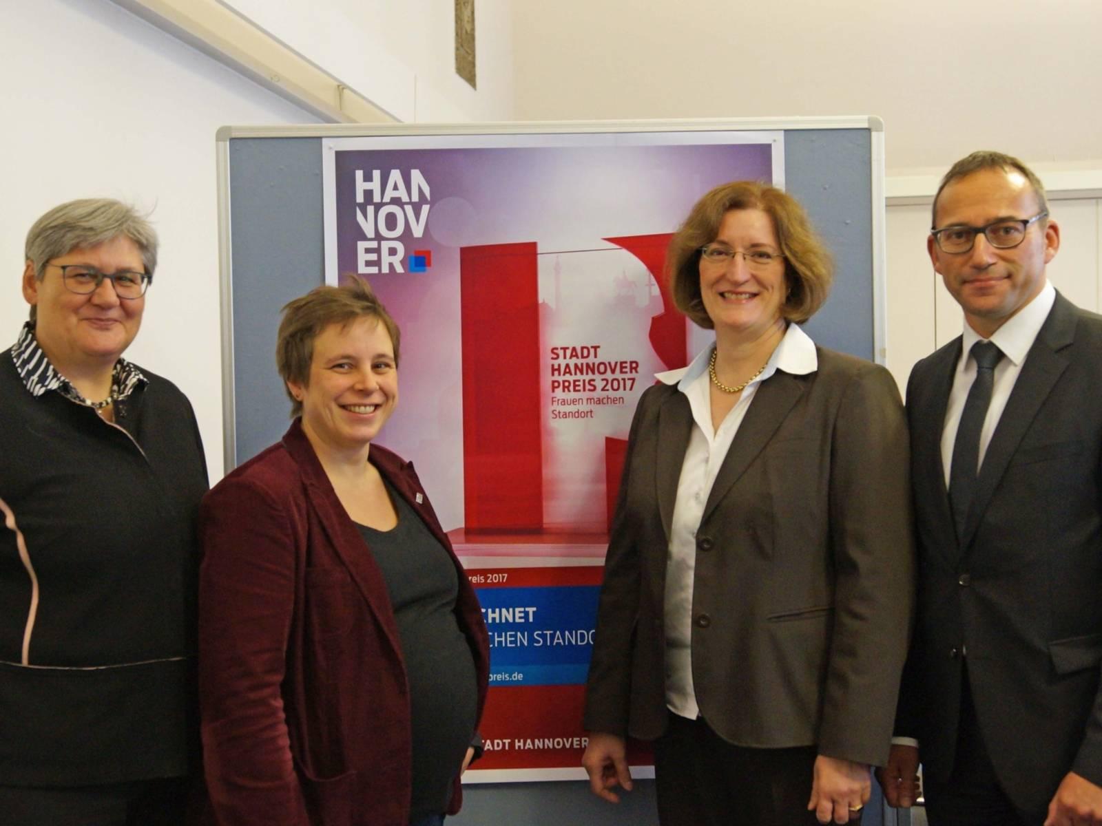 Drei Frauen und ein Mann stehen vor einer Plakatwand.