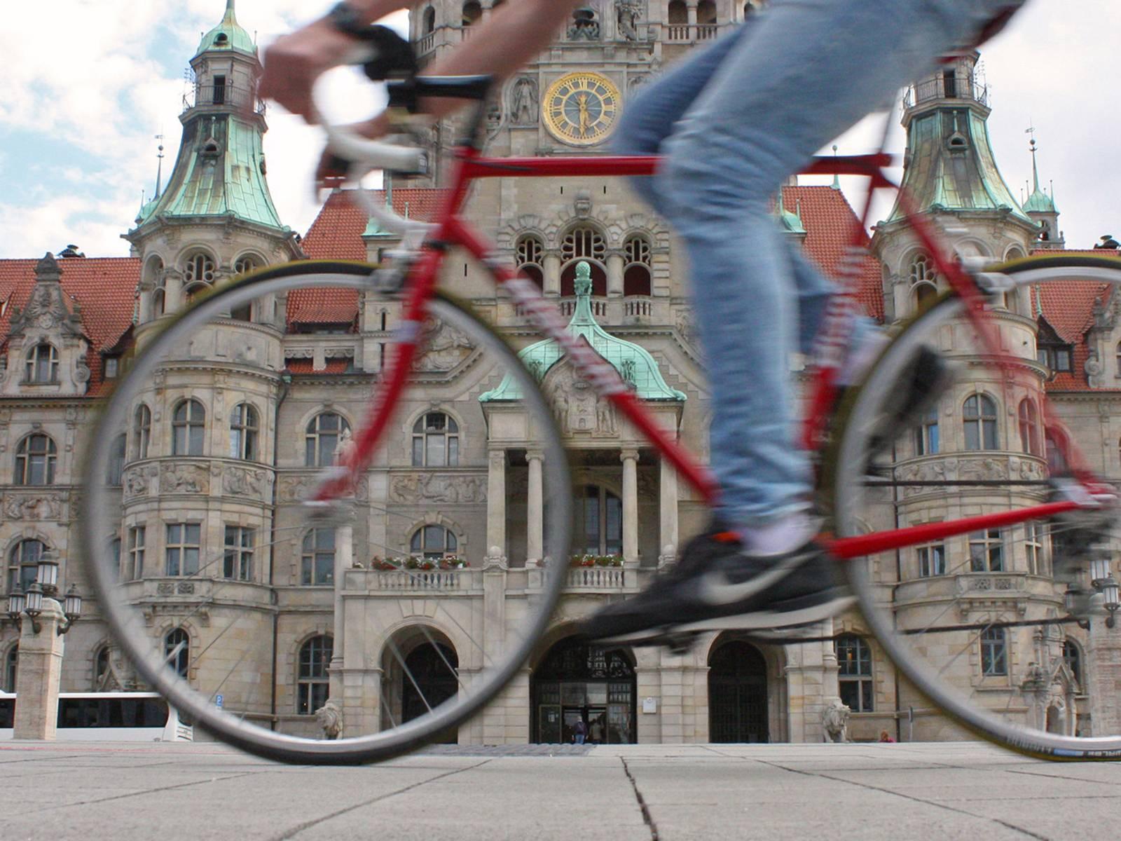 Ein Radfahrer, der an einem Gebäude vorbeifährt.
