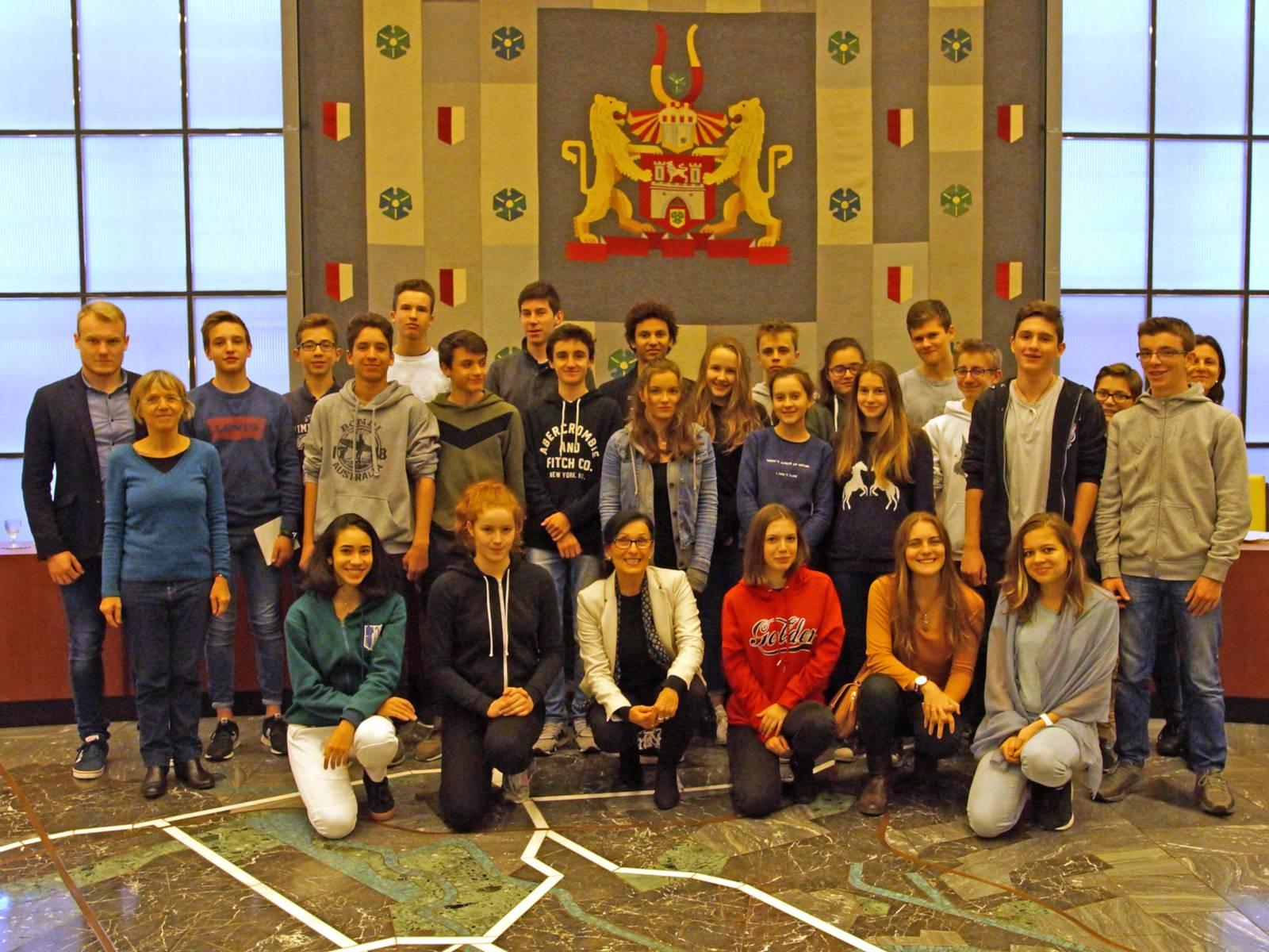 Schülerinnen und Schüler und Erwachsene in einem Saal.