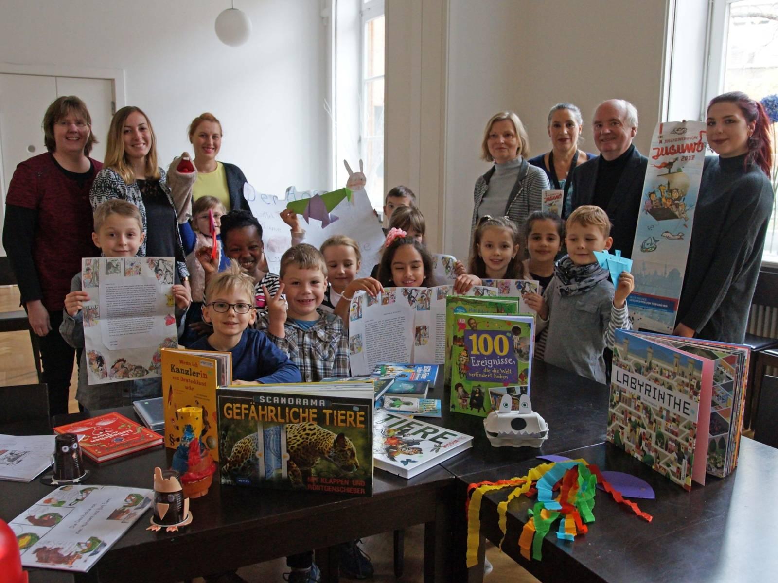 Eine Gruppe Kinder an einem Tisch voll mit Büchern, hinter ihnen steht eine Gruppe Erwachsener.