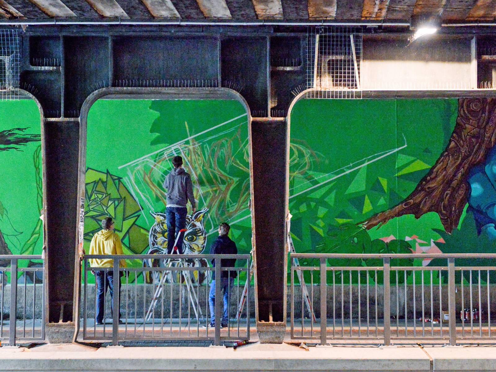 Drei Menschen die ein Graffiti an die Wand einer Unterführung malen.