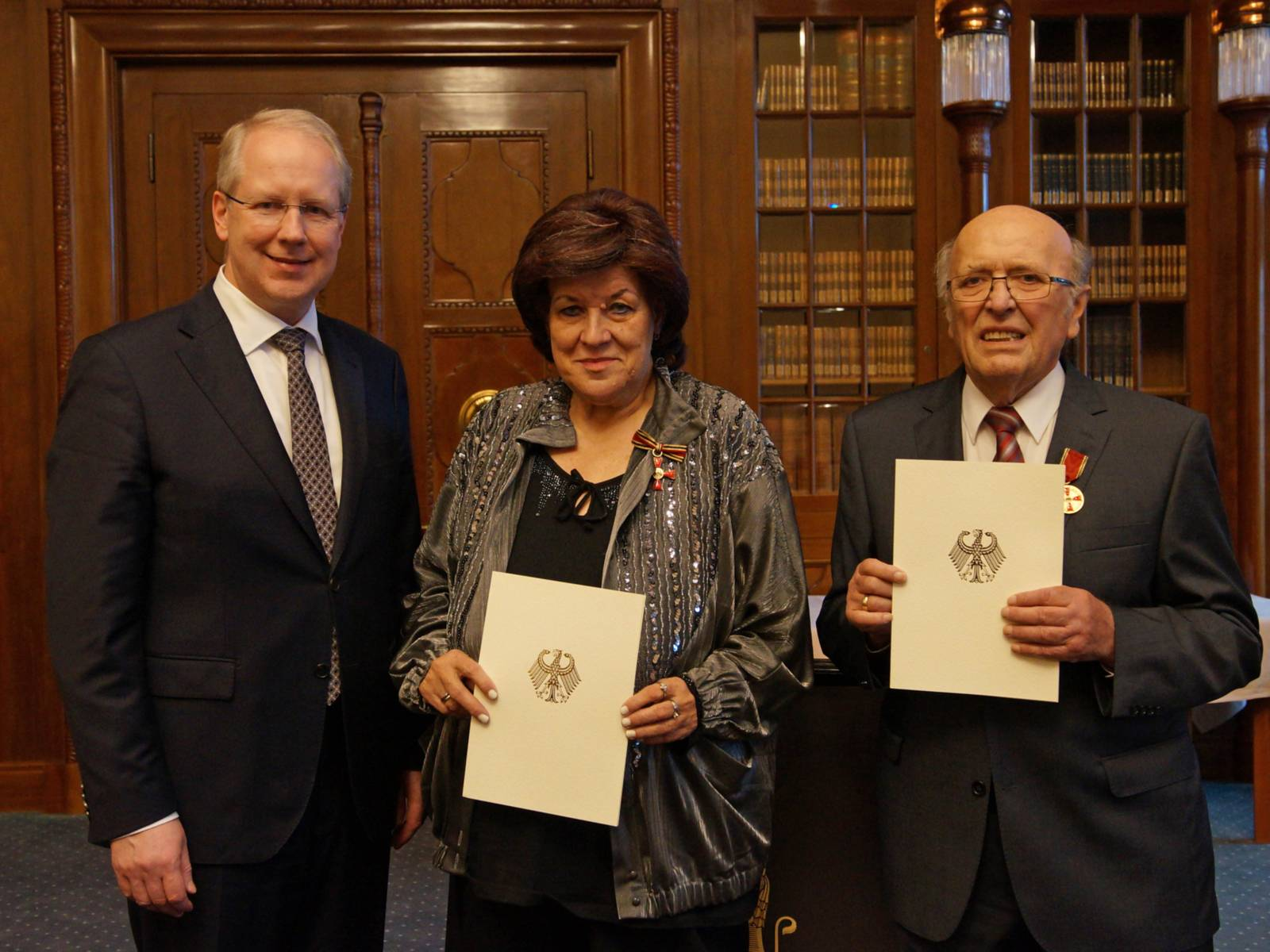 Ein Mann sowie eine Frau mit Urkunde und ein Mann mit Urkunde.