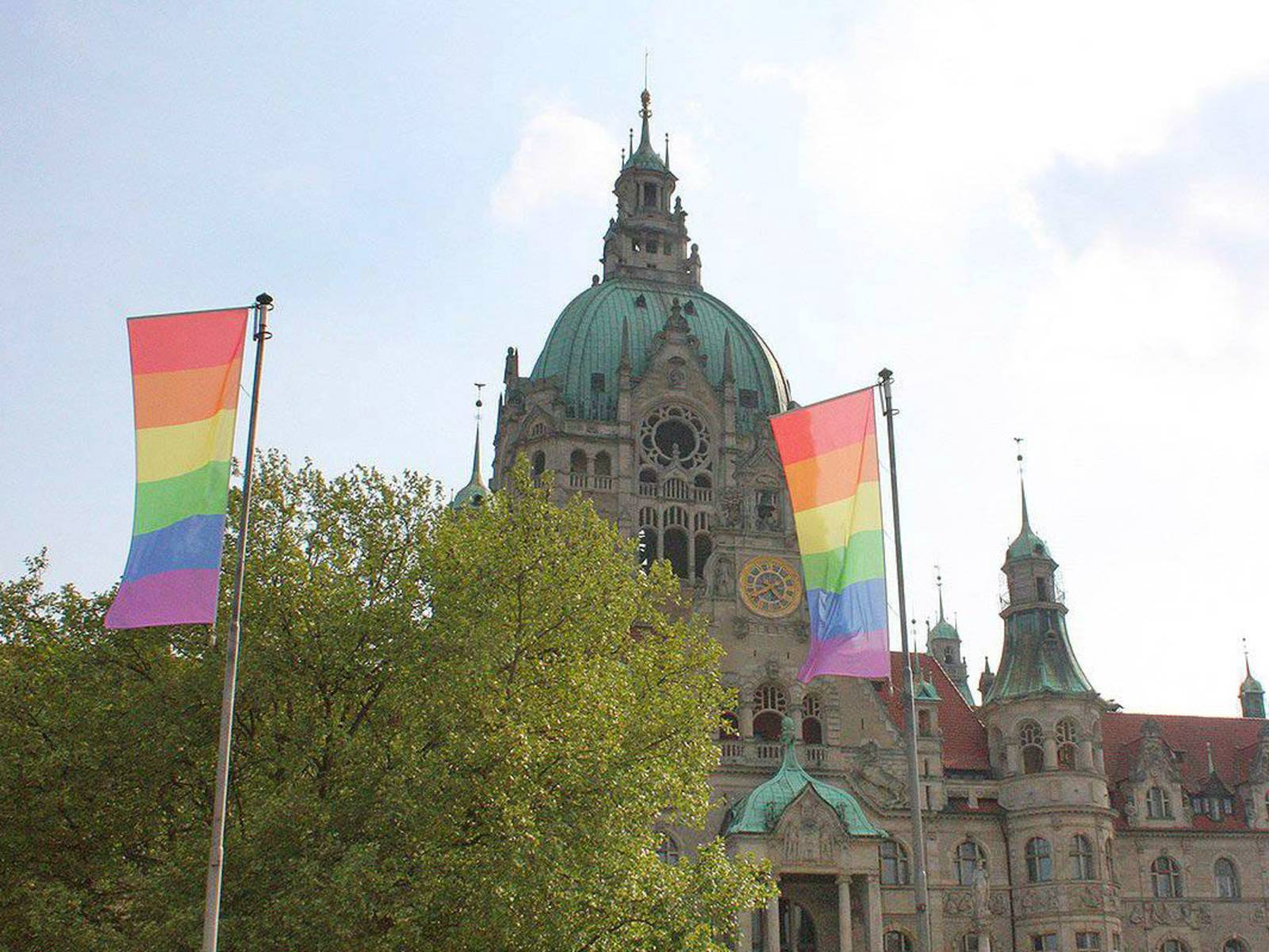 Regenbogen-Flaggen vor einem Gebäude.