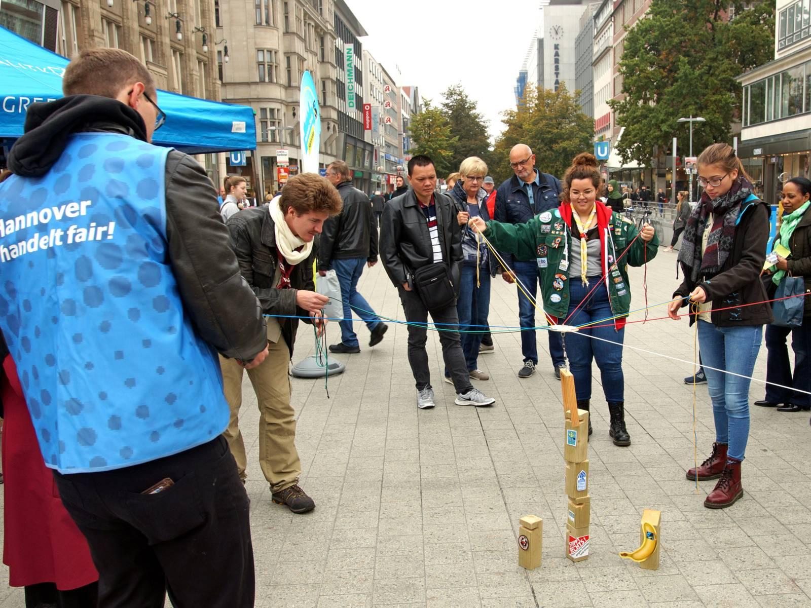 Menschen in einer Fußgängerzone, die junge Leute bei einem Spiel beobachten.