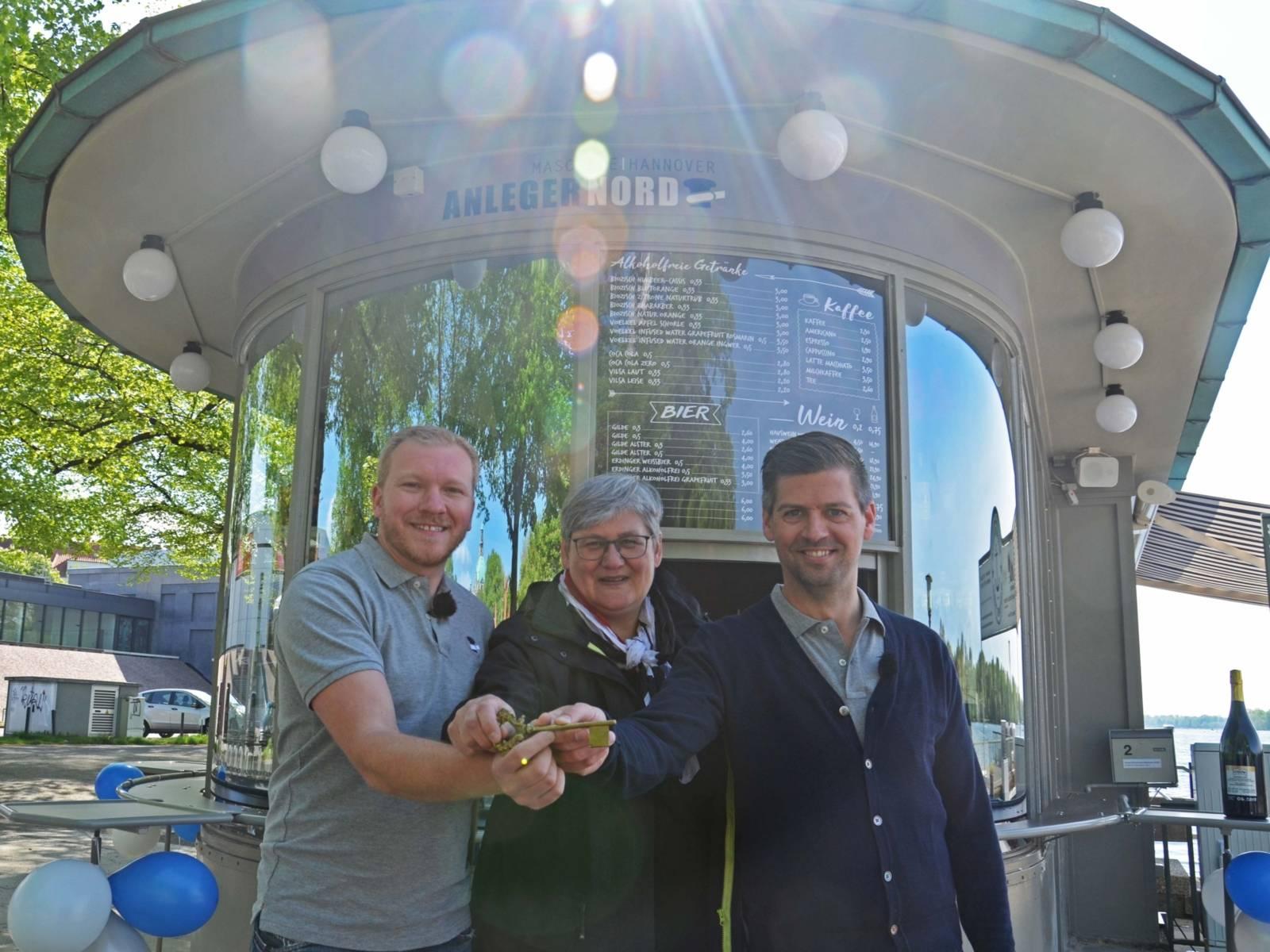 Zwei Männer und eine Frau mit einem goldenen Schlüssel.