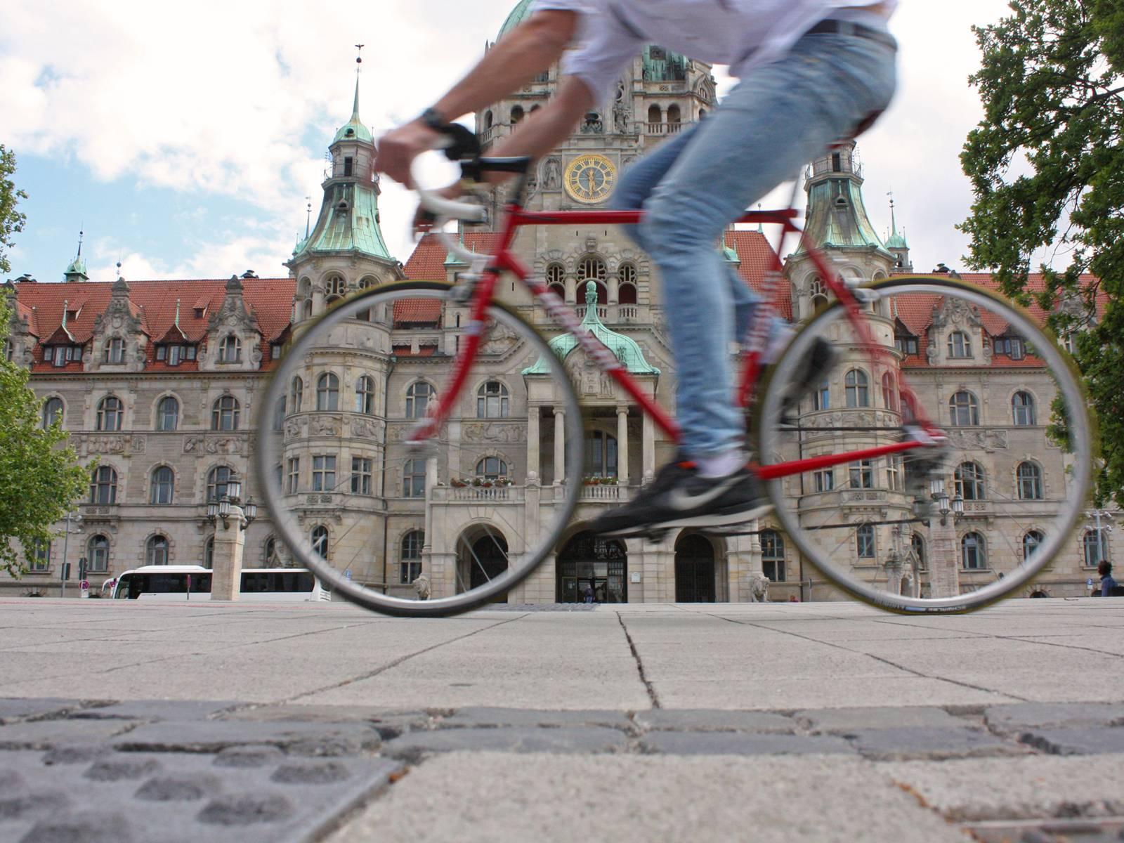 Radfahrer vor einem Rathaus.