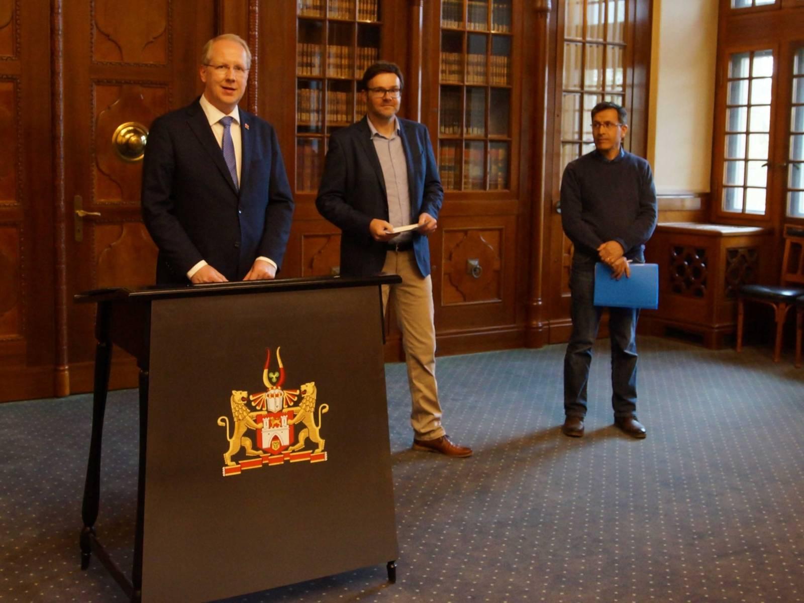Drei Männer in einer Amtsstube.