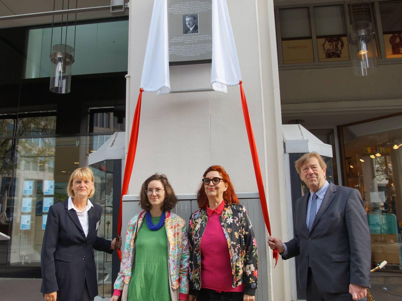Drei Frauen und ein Mann stehen vor einer gerade enthüllten Stadttafel.