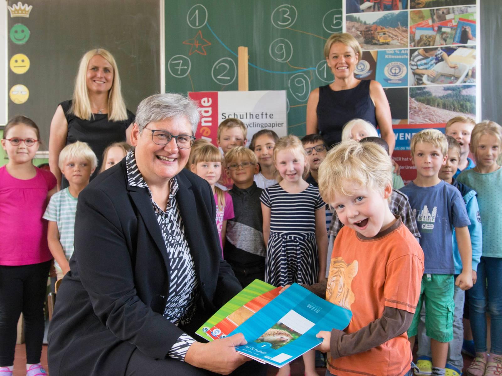 Eine Frau und ein Kind halten Schulhefte in die Kamera, im Hintergrund steht die restliche Schulklasse vor einer Tafel