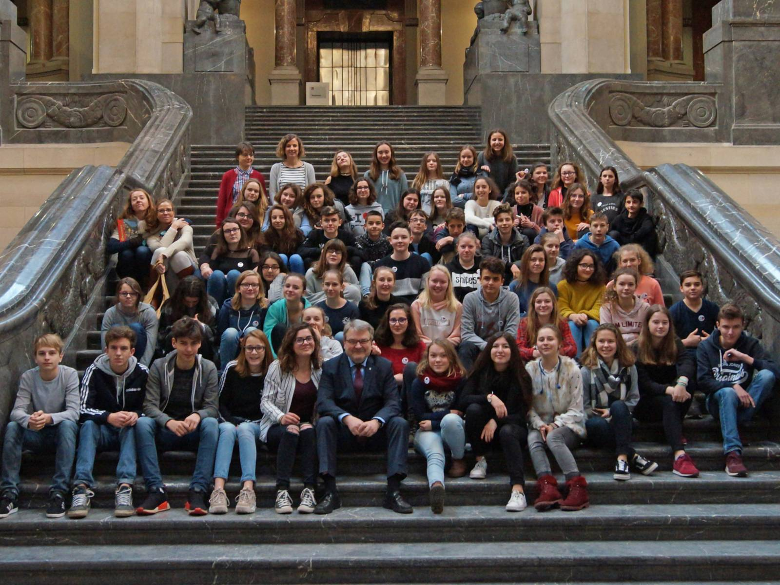 Besuchergruppe junge Leute auf einer Treppe sitzend in einer Halle.