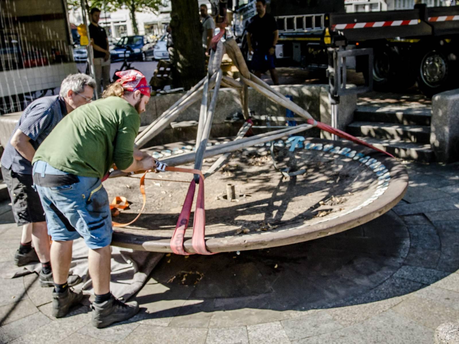 Bauarbeiter heben einen Brunnenschale mit einem Kran.