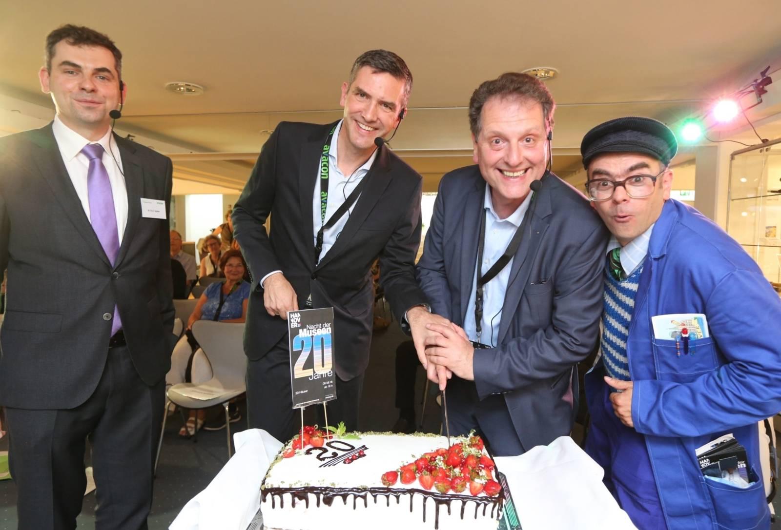 Vier Männer, die eine Torte anschneiden.