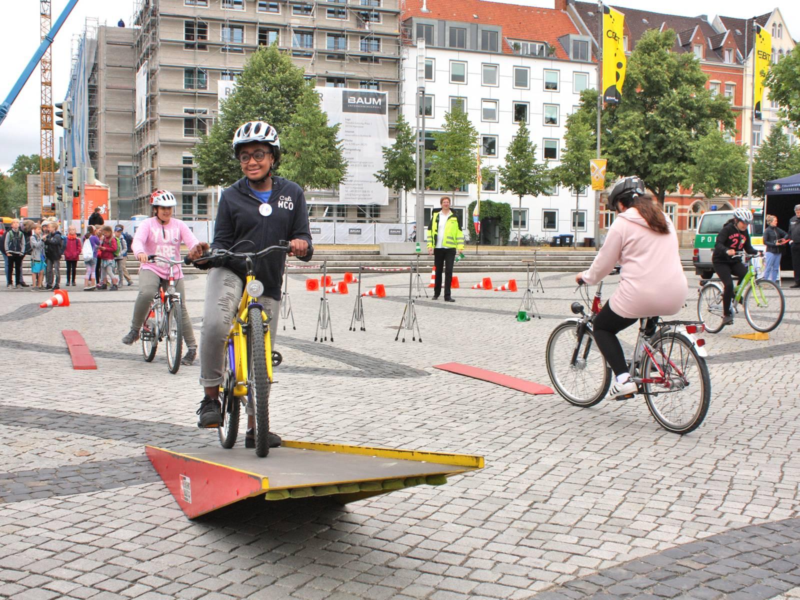 Ein Mädchen fährt mit einem Fahrrad durch einen Parcours