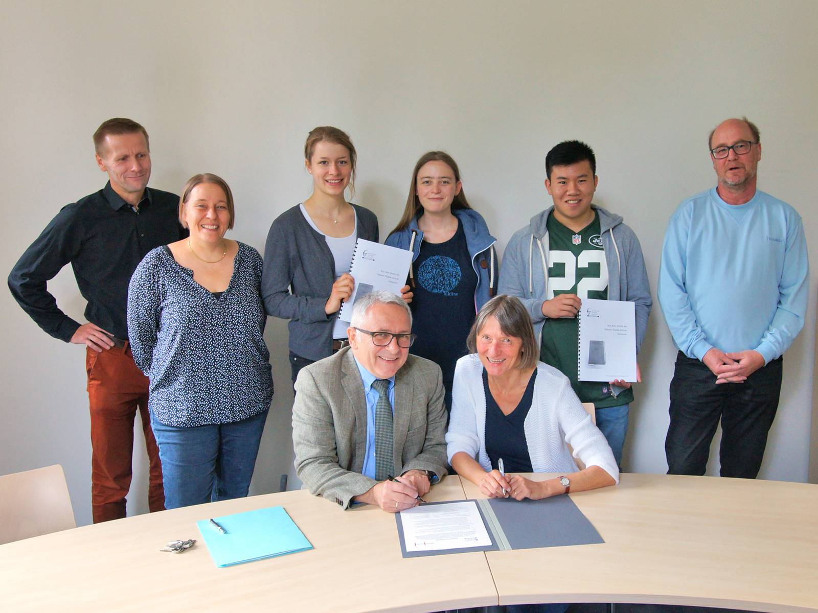 Zwei Personen sitzen an einem Tisch und unterzeichnen ein Dokument, dahinter stehen sechs weitere Personen