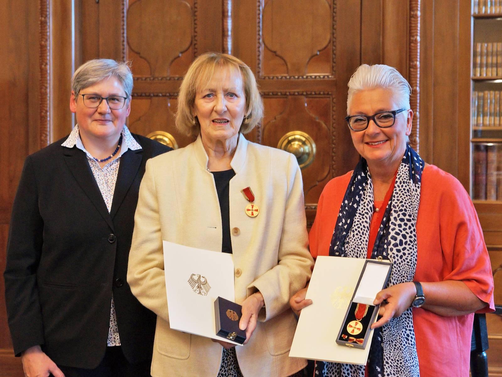 Drei Frauen in einer Amtsstube.