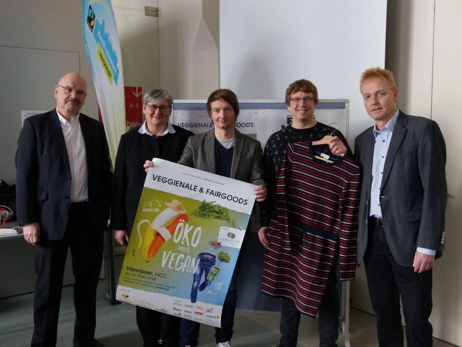 Vier Männer und eine Frau stehen vor einer Plakatwand. Einer hält ein Werbeplakat und ein anderer ein Kleid in den Händen