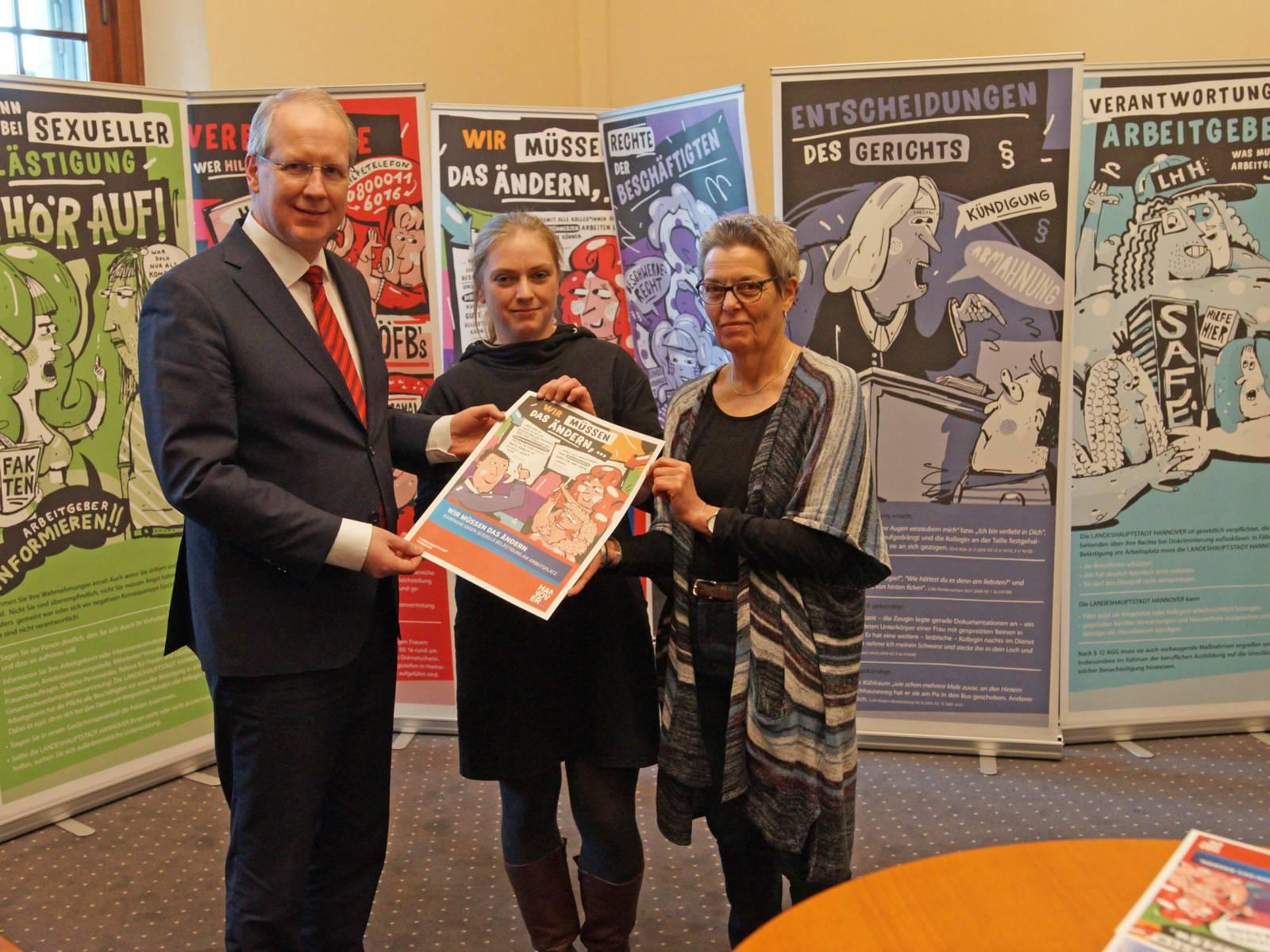 Ein Mann und zwei Frauen halten ein kleines Plakat