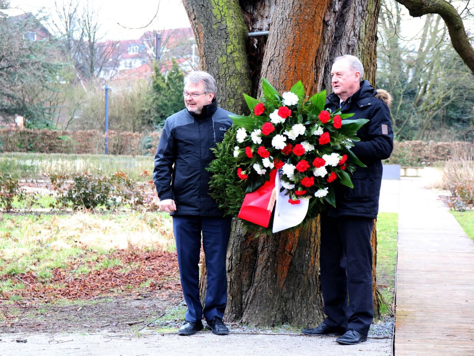 Zwei Männer stehen mit einem Blumenkranz vor einem Baum.