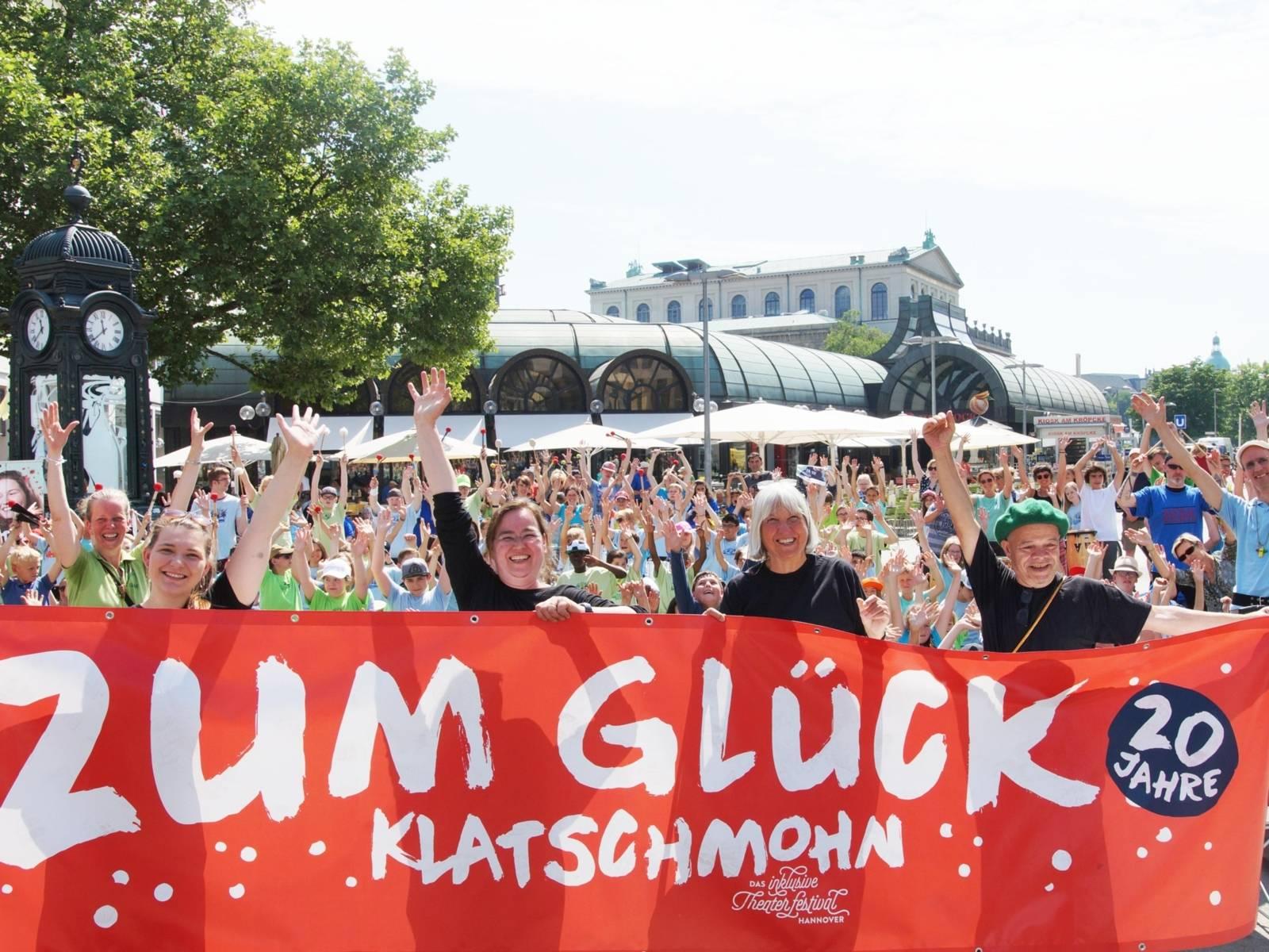 Menschen mit einem großen Banner an einem öffentlichen Platz.