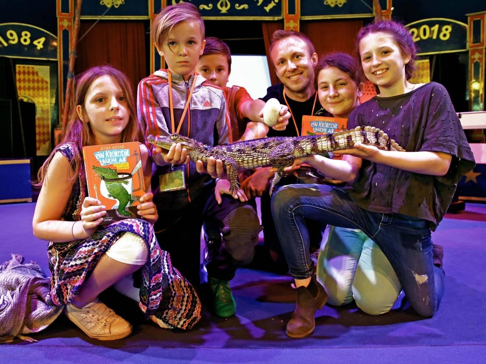 Zwei Junges, drei Mädchen, ein Mann und ein Kaiman in einem Zirkuszelt.
