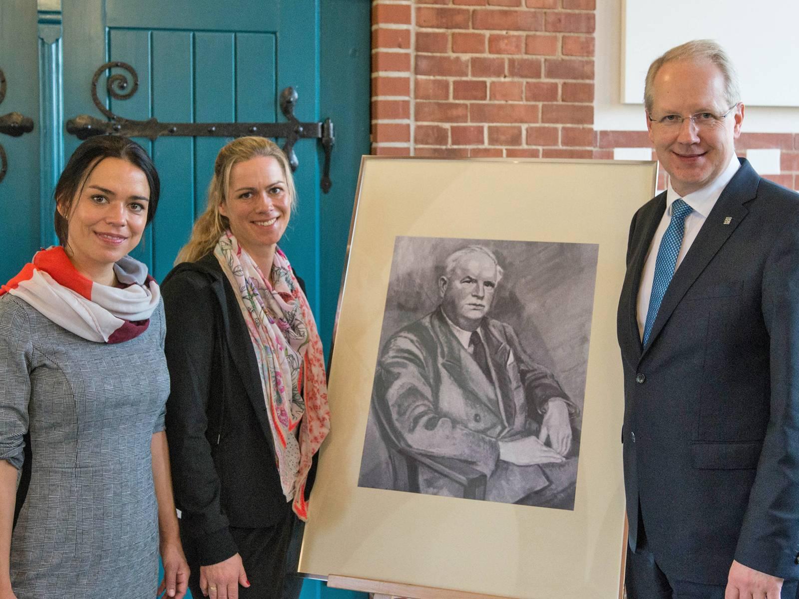 Drei Personen neben einer Staffelei, auf der ein Portrait eines Mannes steht