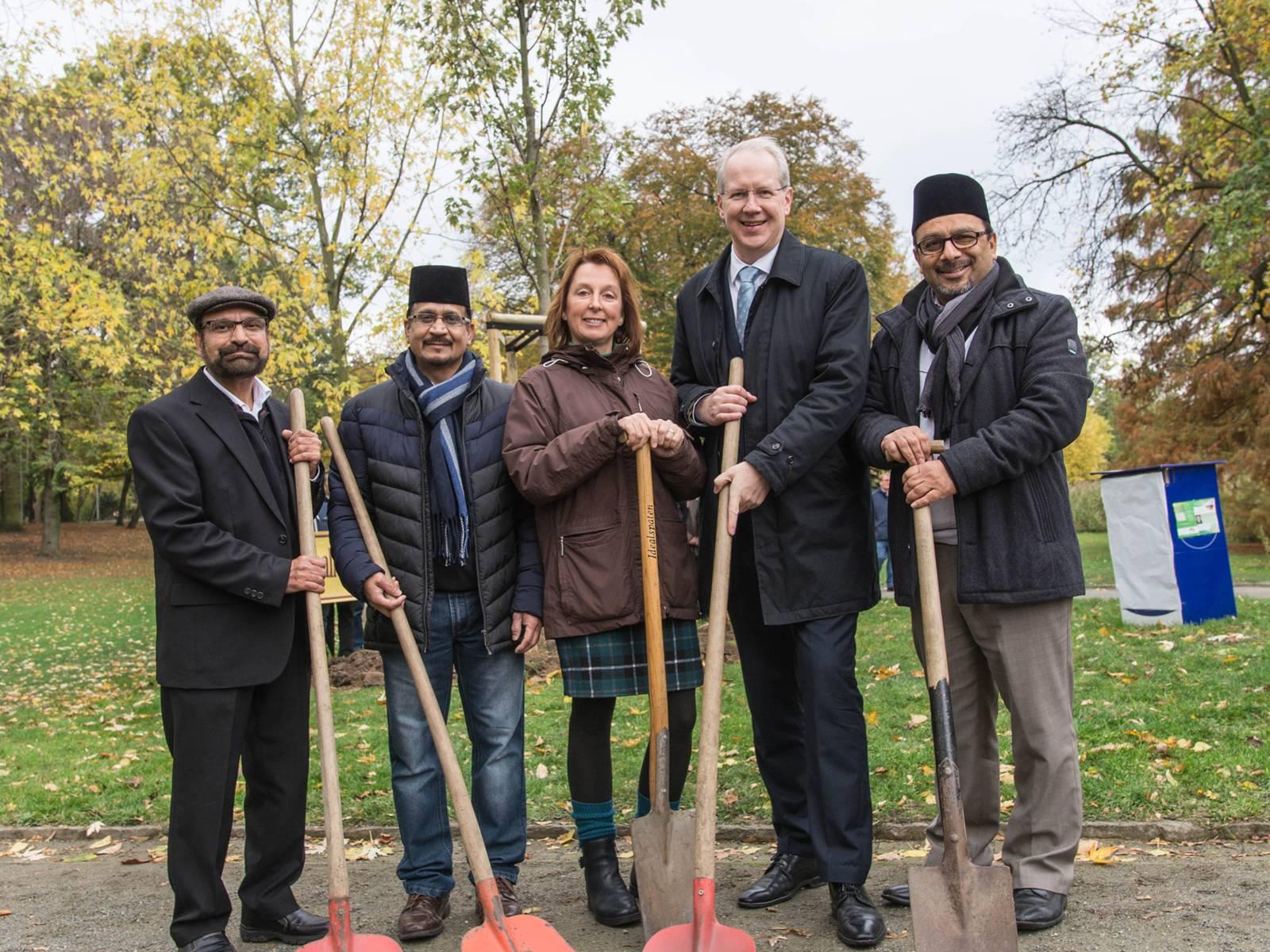 Fünf Personen mit Schaufeln vor einem neu gepflanzten Baum