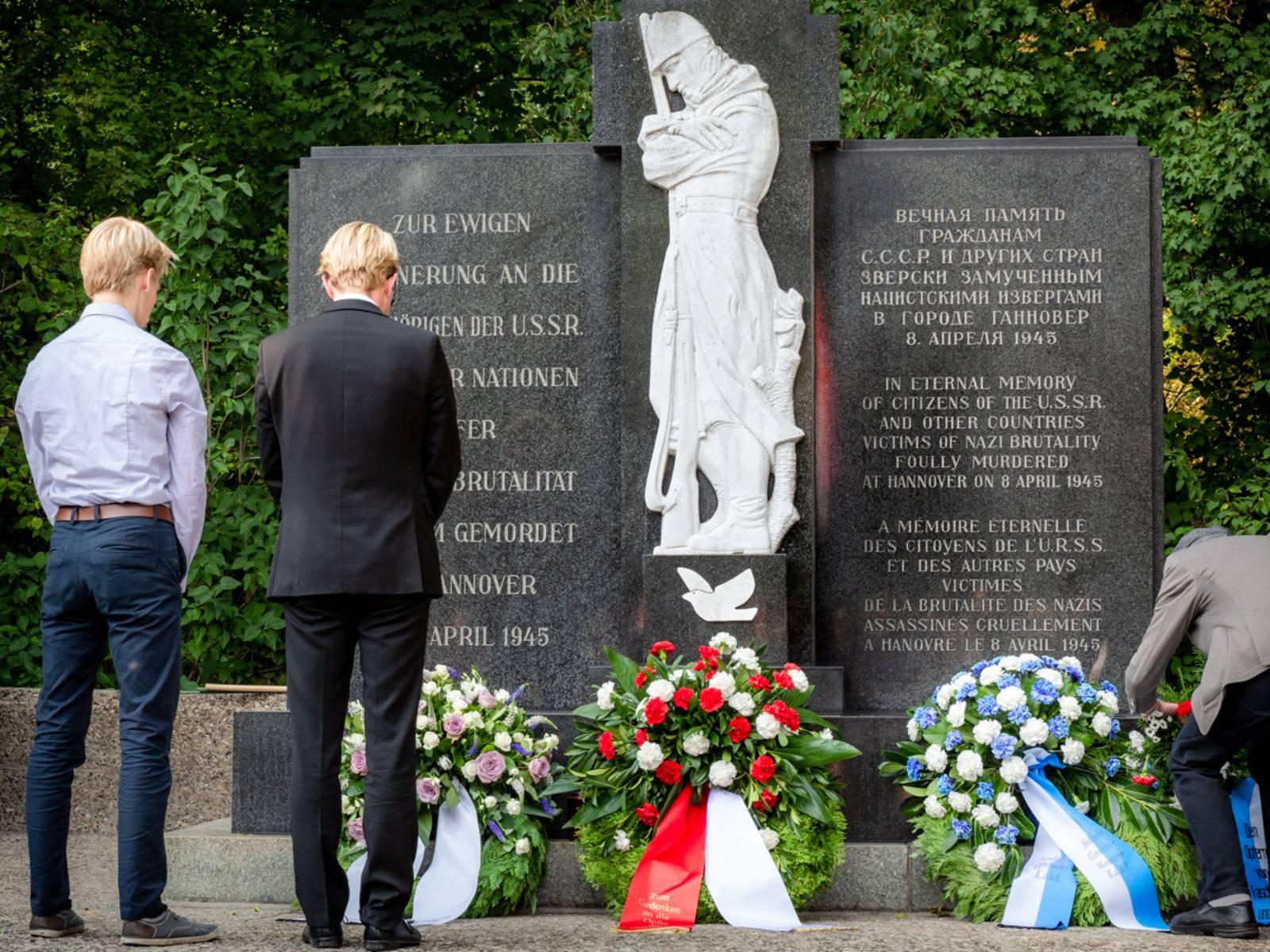Zwei junge Menschen stehen vor dem Mahnmal auf dem Ehrenfriedhof am Maschsee-Nordufer und halten inne