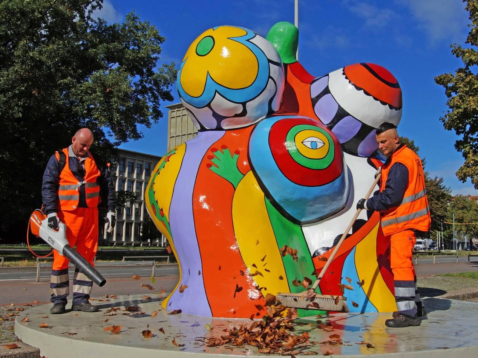 Zwei Männer, die eine Skulptur reinigen.