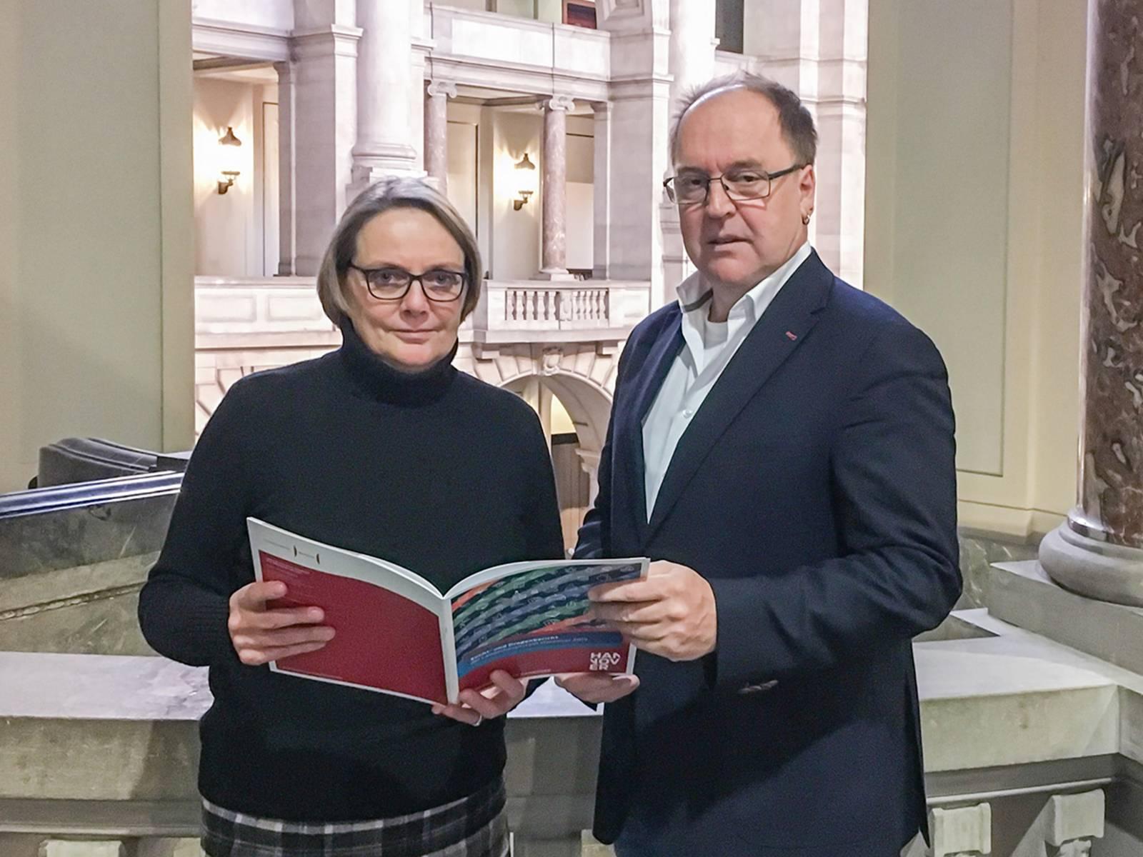 Eine Frau und ein Mann stehen an einer Balustrade, die Frau hält eine Broschüre in der Hand