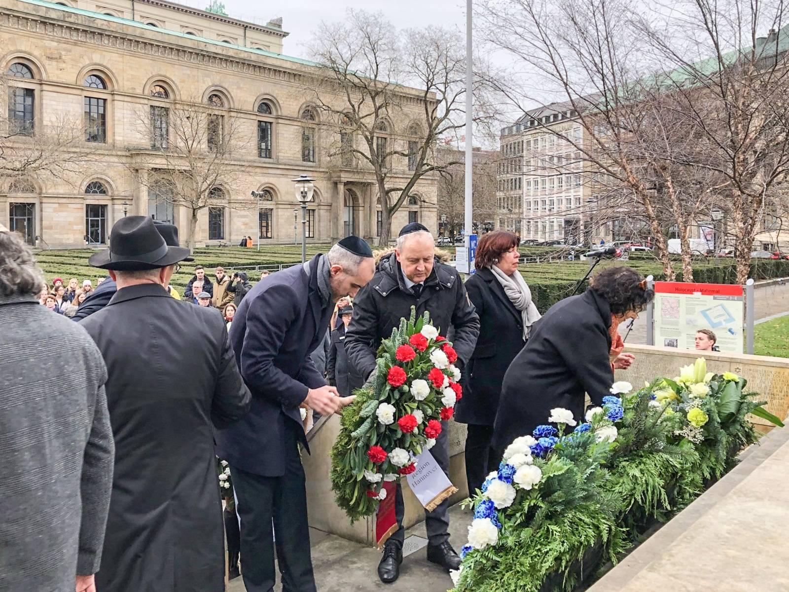 Menschen in Gedenken vor einem Mahnmal voller Blumen.