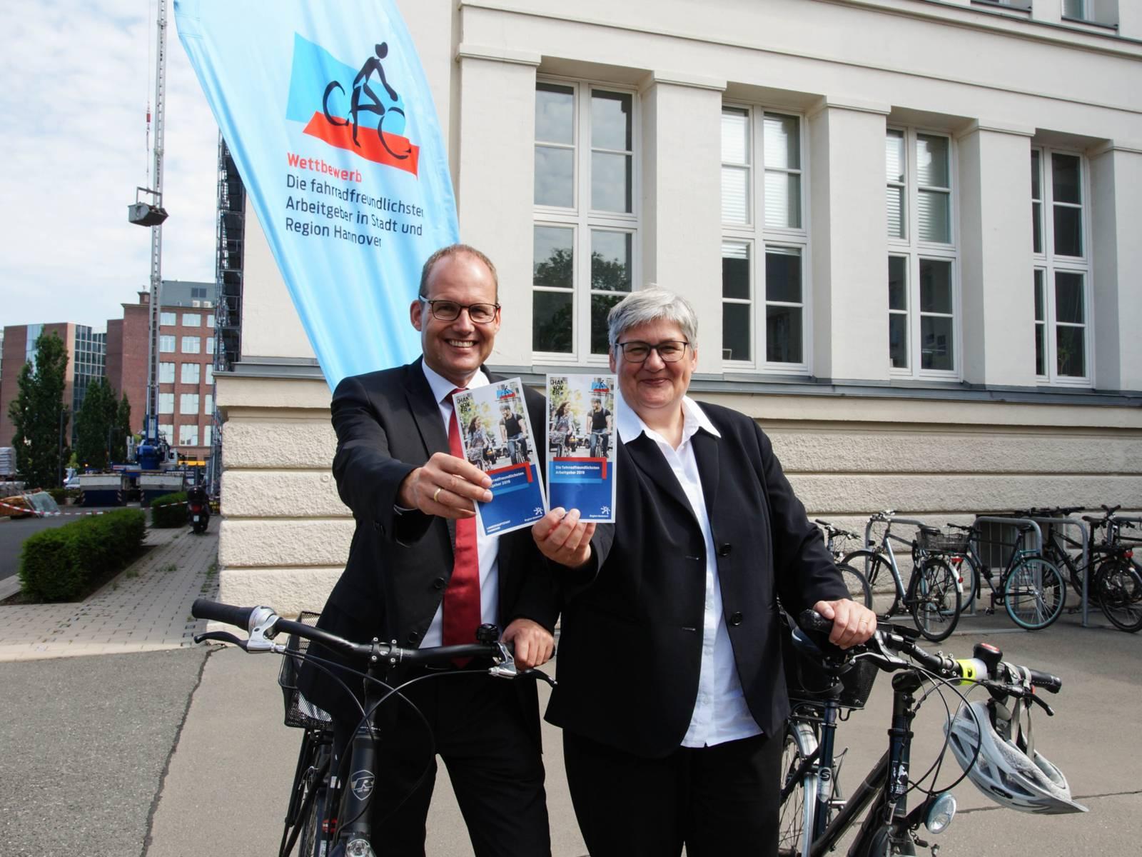 Ein Mann und eine Frau mit Fahrrädern. Sie zeigen einen Flyer.