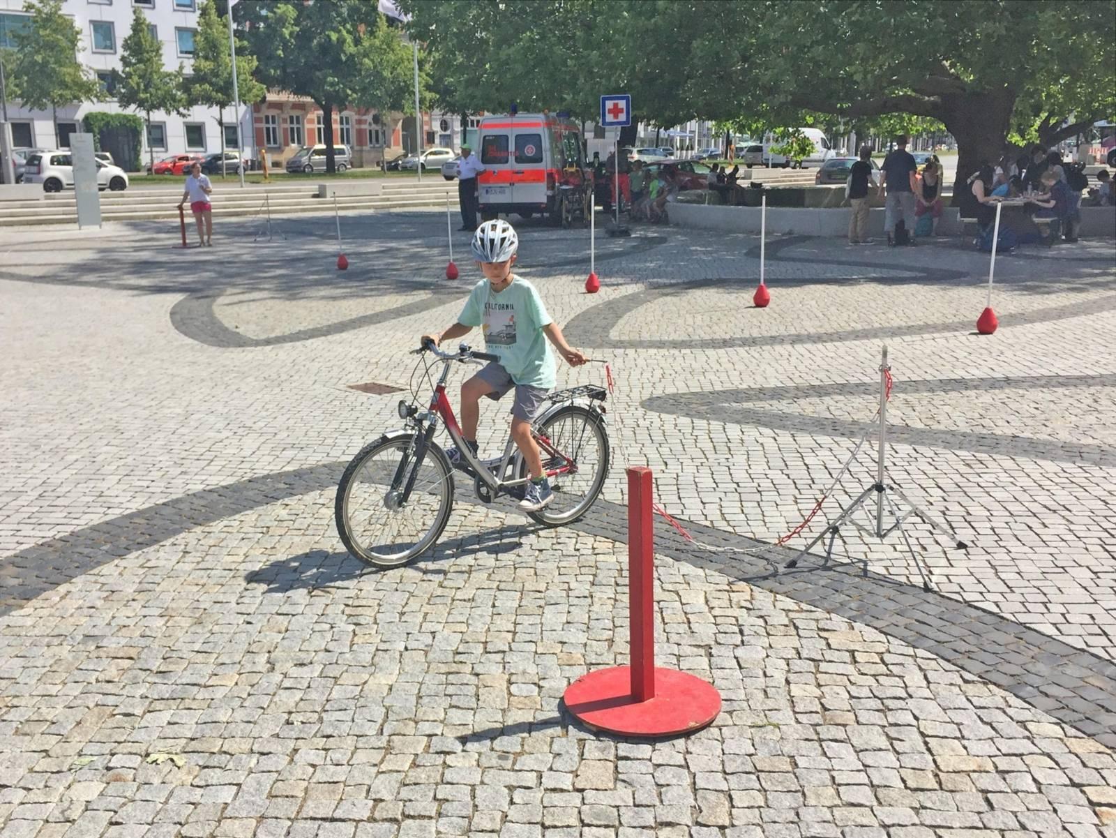 Kind, das mit einem Fahrrad auf einem Platz fährt.