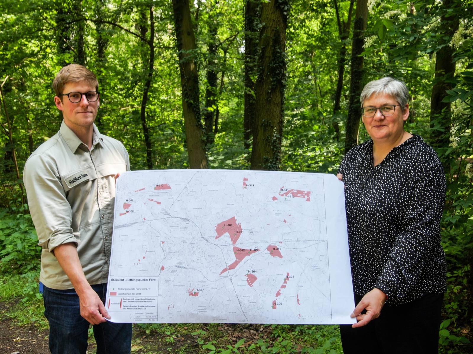 Ein Mann und eine Frau mit einer Karte im Wald.