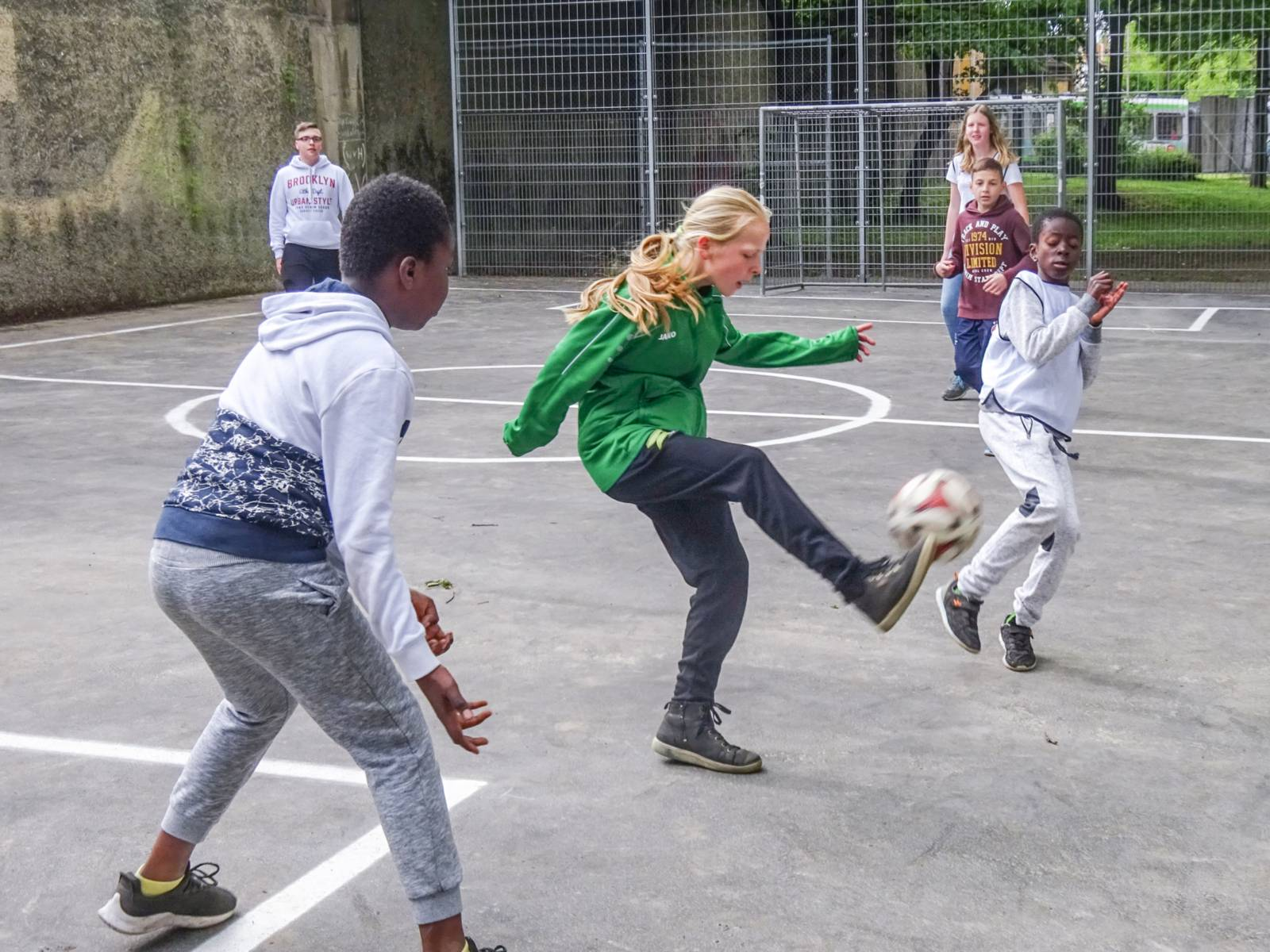 Kinder spielen Fußball auf einem Bolzplatz