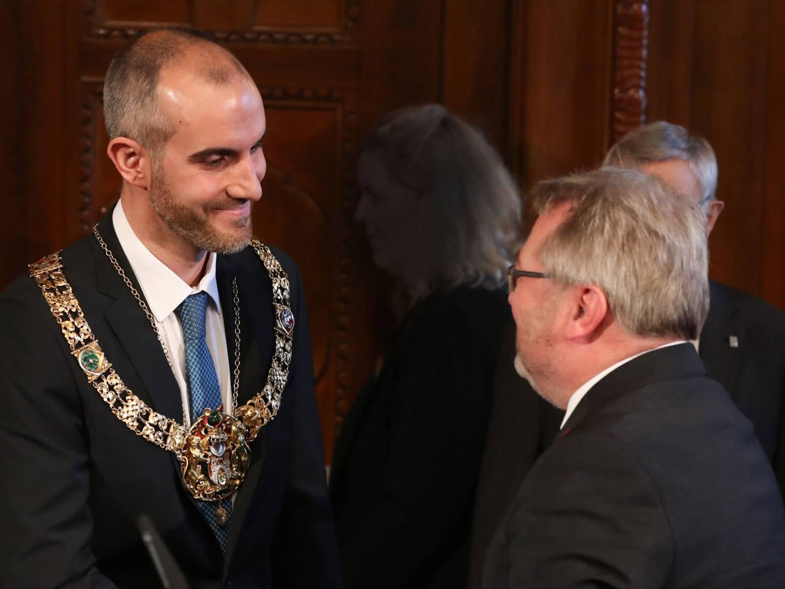 Ein Mann legt einem anderen Mann eine goldene Amtskette an