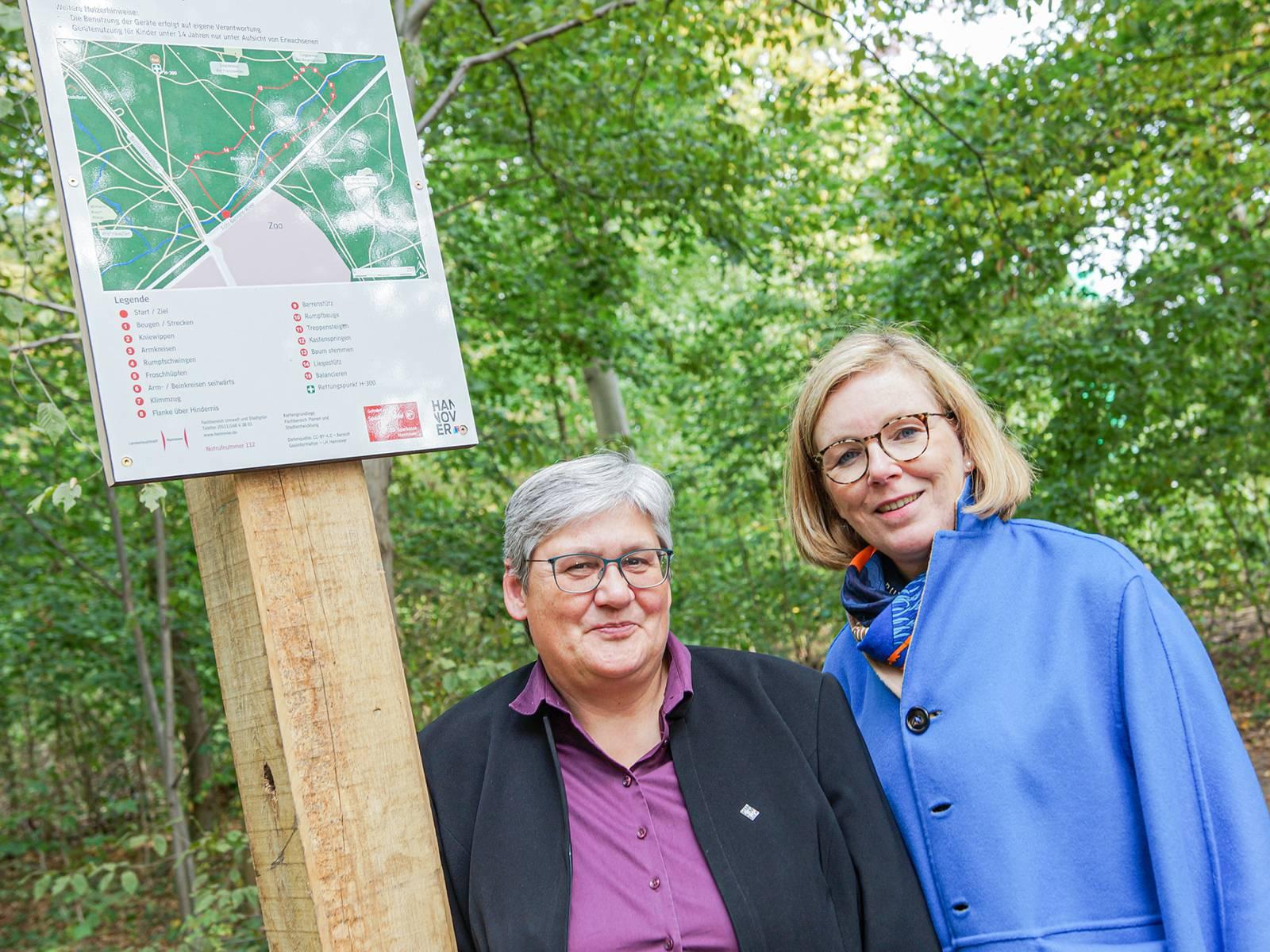 Zwei Frauen an einem Hinweisschild für einen Trimm-dich-Pfad