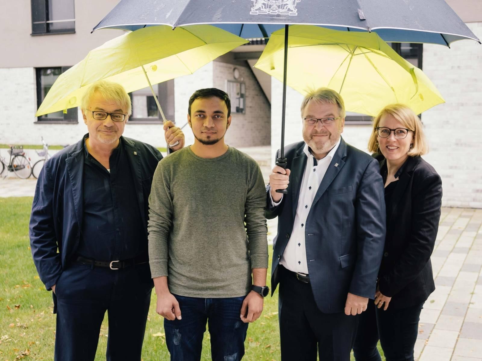 Drei Männer und eine Frau unter Regenschirmen.