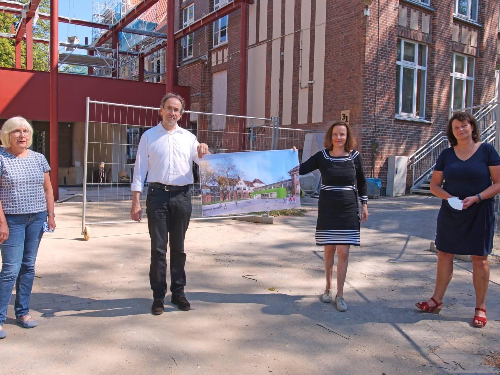 Vier Personen auf einem Hof. Sie halten ein Bild, das eine Schule zeigt.