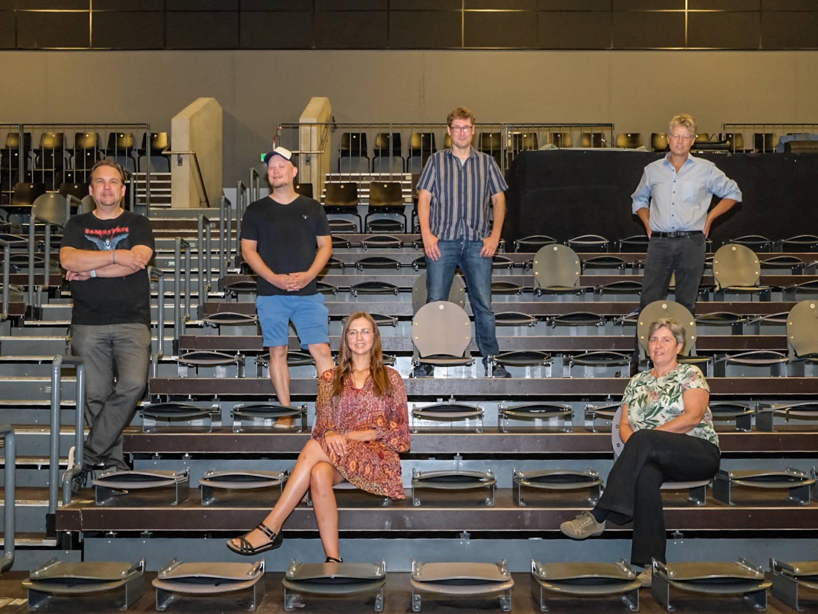 Sechs Personen stehen bzw. sitzen auf der Tribüne in einem Saal