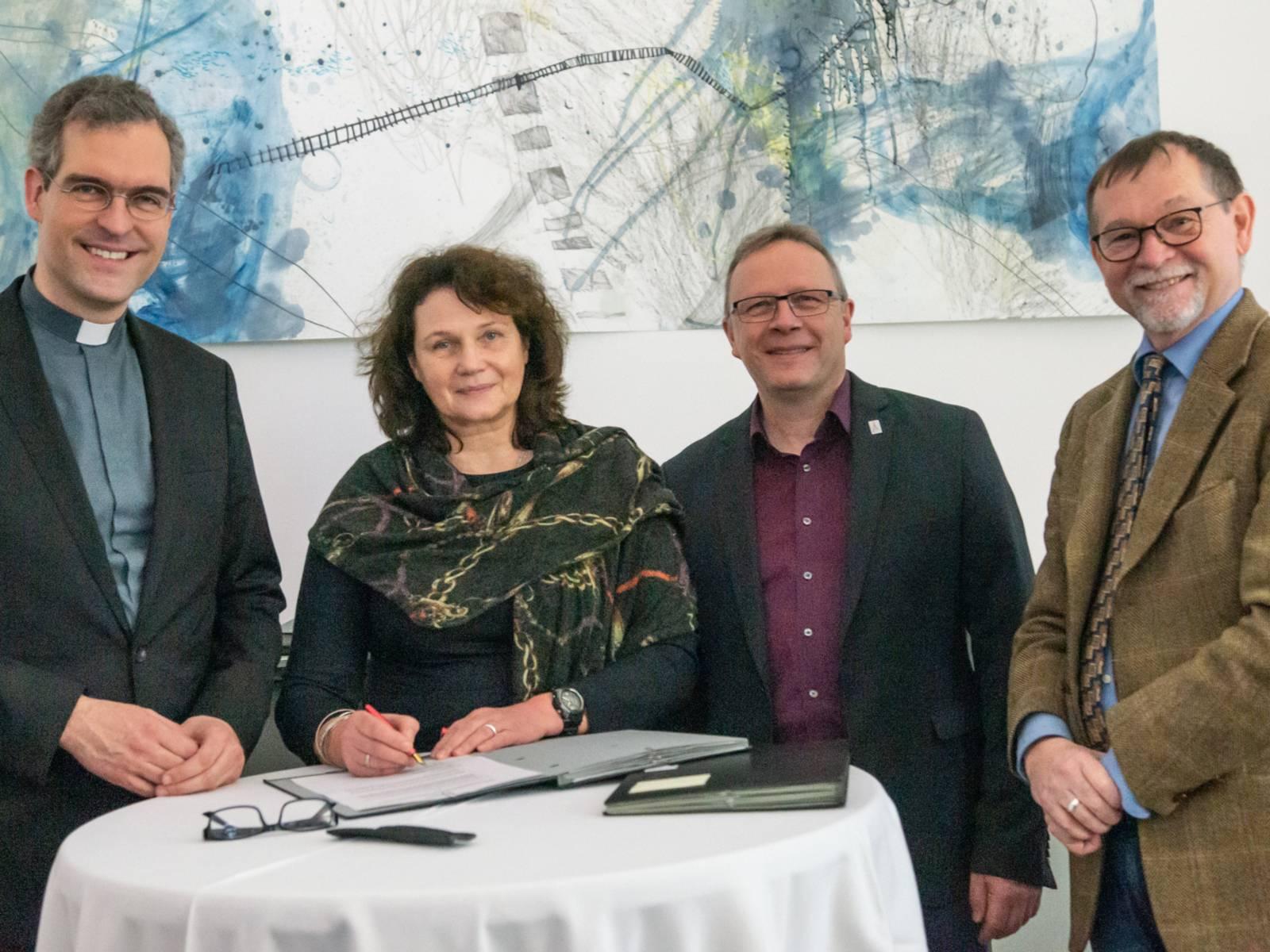 Vier Personen stehen an einem runden Tisch, auf dem Dokumente liegen