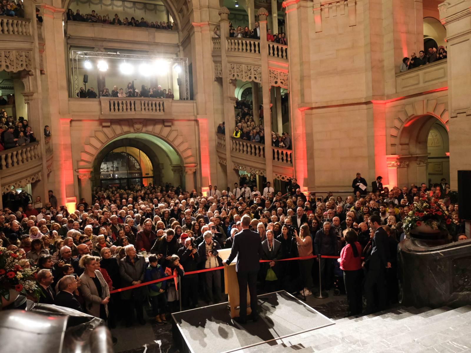 Menschen in einer großen Halle, die einem Mann am Rednerpult zuhören.