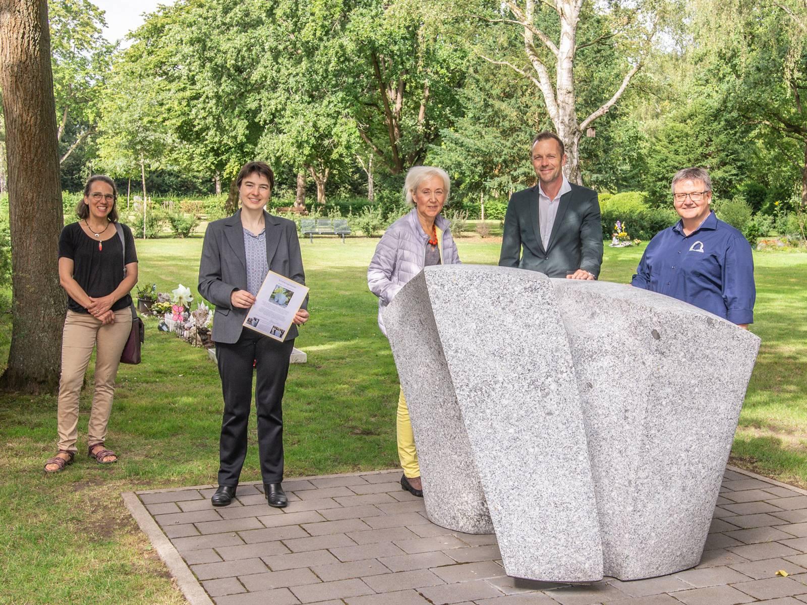 Fünf Personen stehen bei einer Skulptur auf einem Friedhof