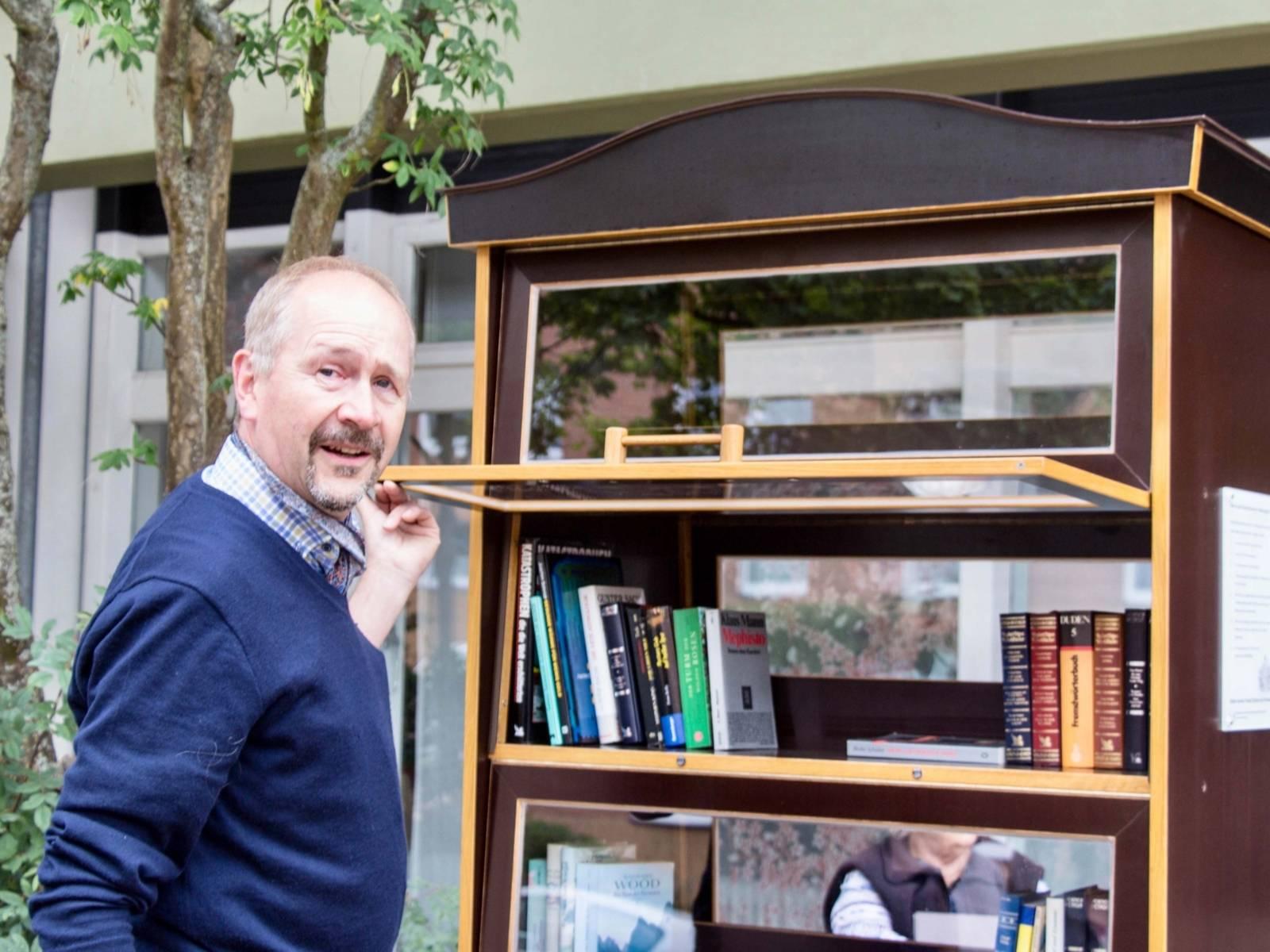 Mann vor einem Schrank mit Büchern.