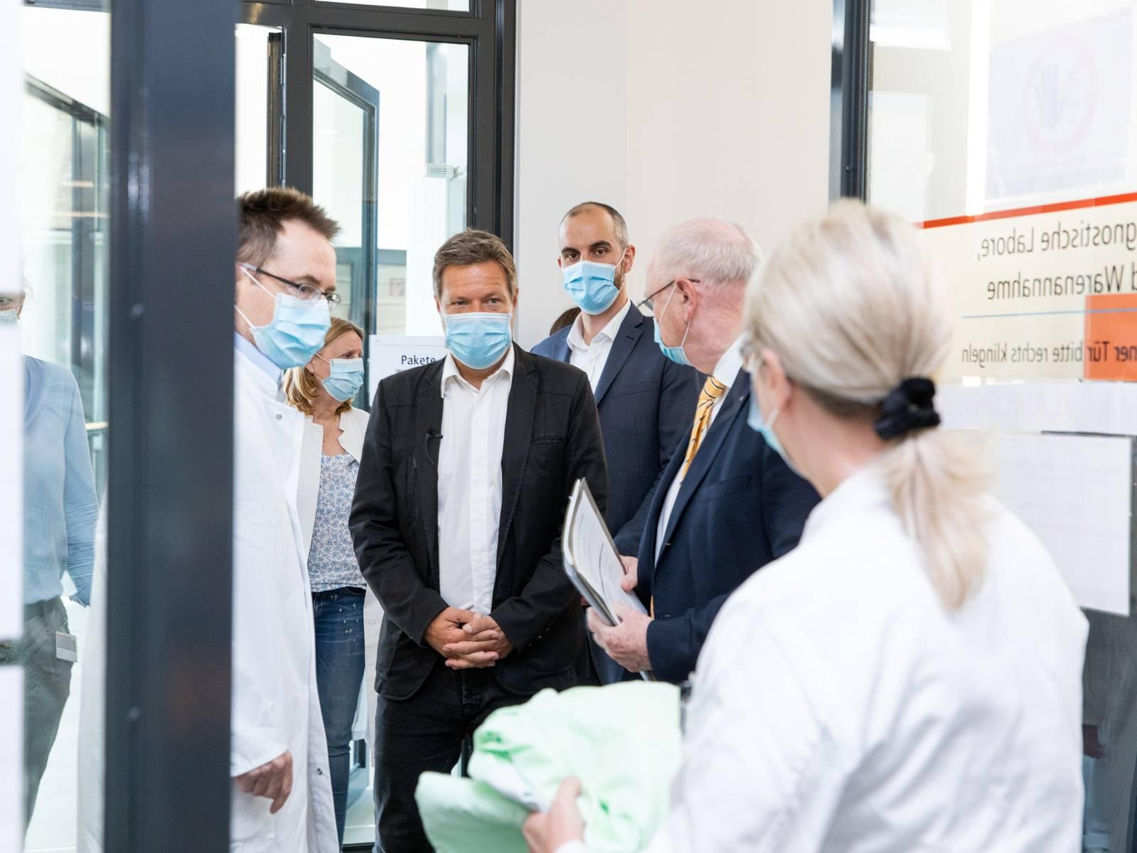 Mehrere Personen mit Schutzmasken in einer Forschungseinrichtung, darunter Oberbürgermeister Belit Onay und Politiker Robert Habeck.