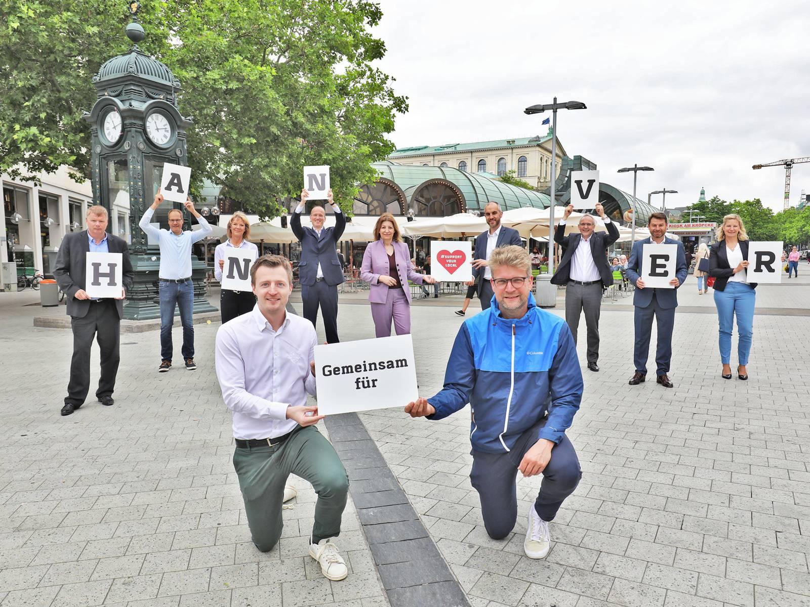 """Elf Personen stehen auf einem Platz und bilden mit Schildern den Schriftzug """"Gemeinsam für Hannover"""""""