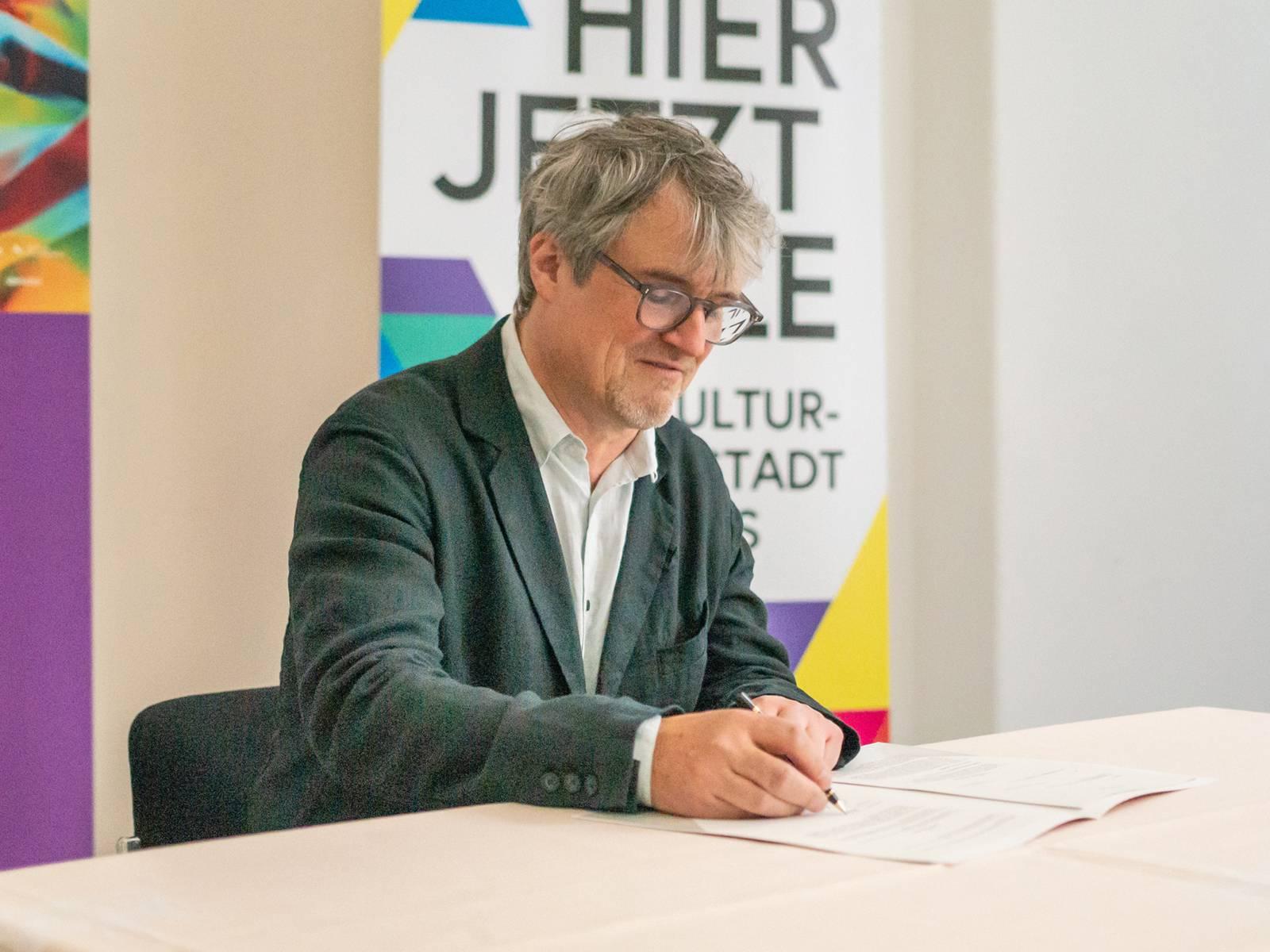 Ein Mann sitzt an einem Tisch und unterschreibt einen Vertrag