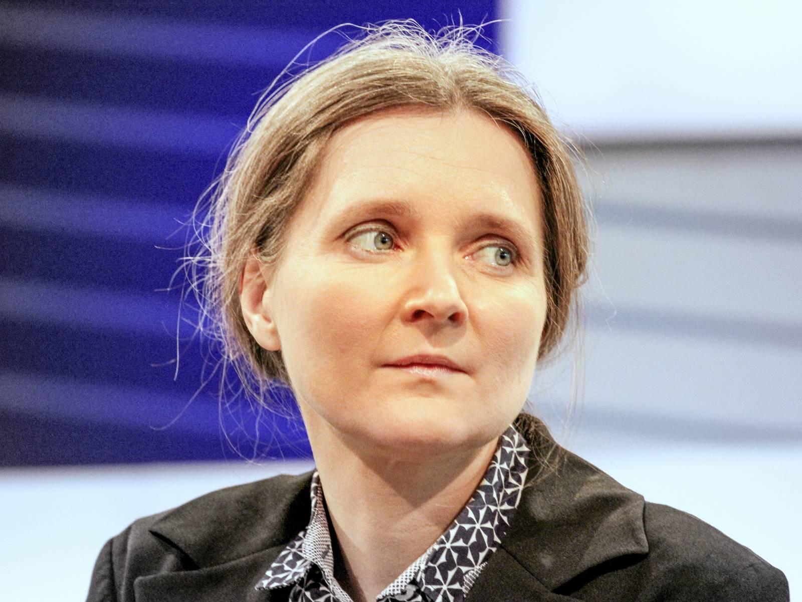 Portrait einer Frau vor einem blau-grauen Hintergrund